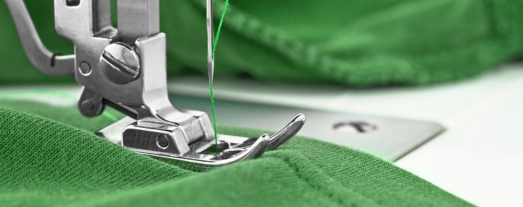 A sewing machine sewing a green fabric.