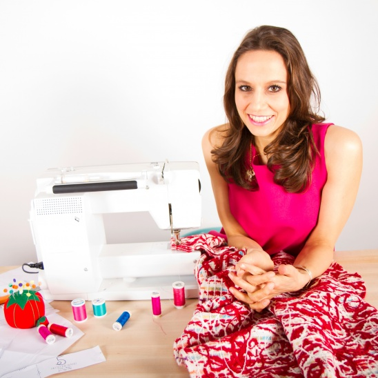 A woman sitting beside a sewing machine and thread.