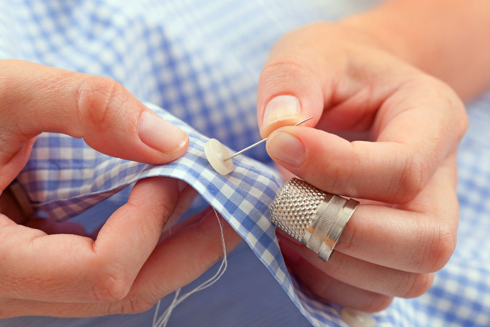 Sewing a button to a shirt.